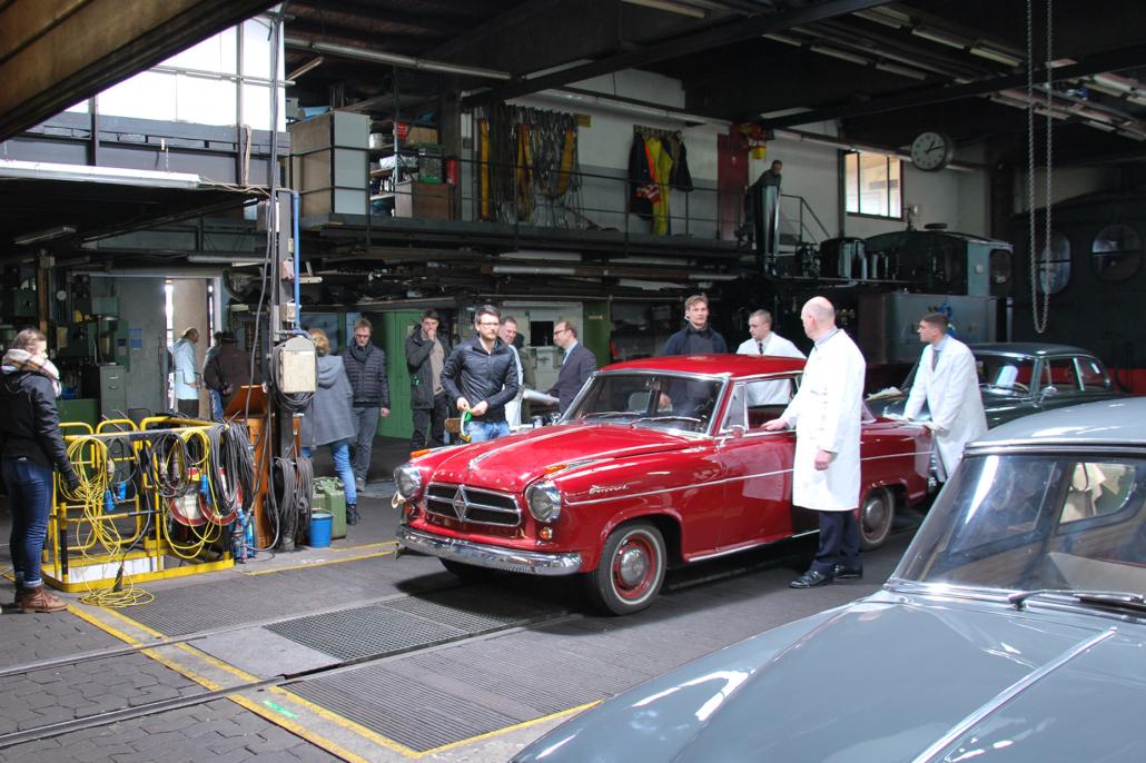 Komparsen (weiße Kittel) und Filmteam bereiten eine Szene in der Werkhalle der Museumsbahn vor.