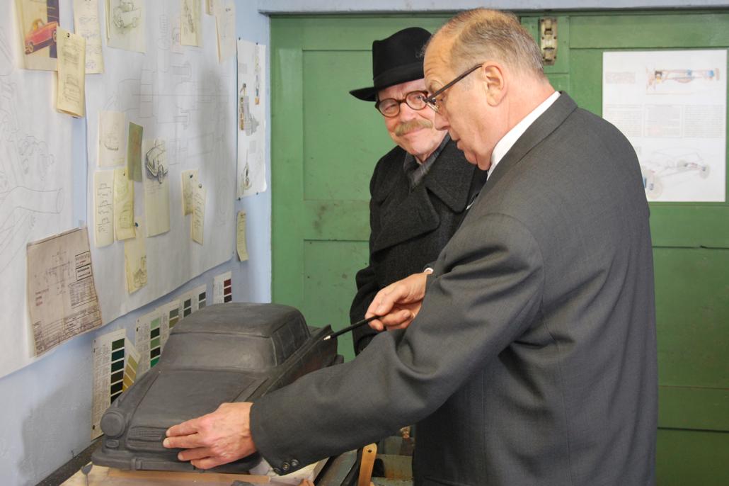 Bürgermeister Wilhelm Kaisen (links/Jürgen Heinrich) lässt sich von Carl Borgward (Thomas Thieme) Details am Automodell erklären.