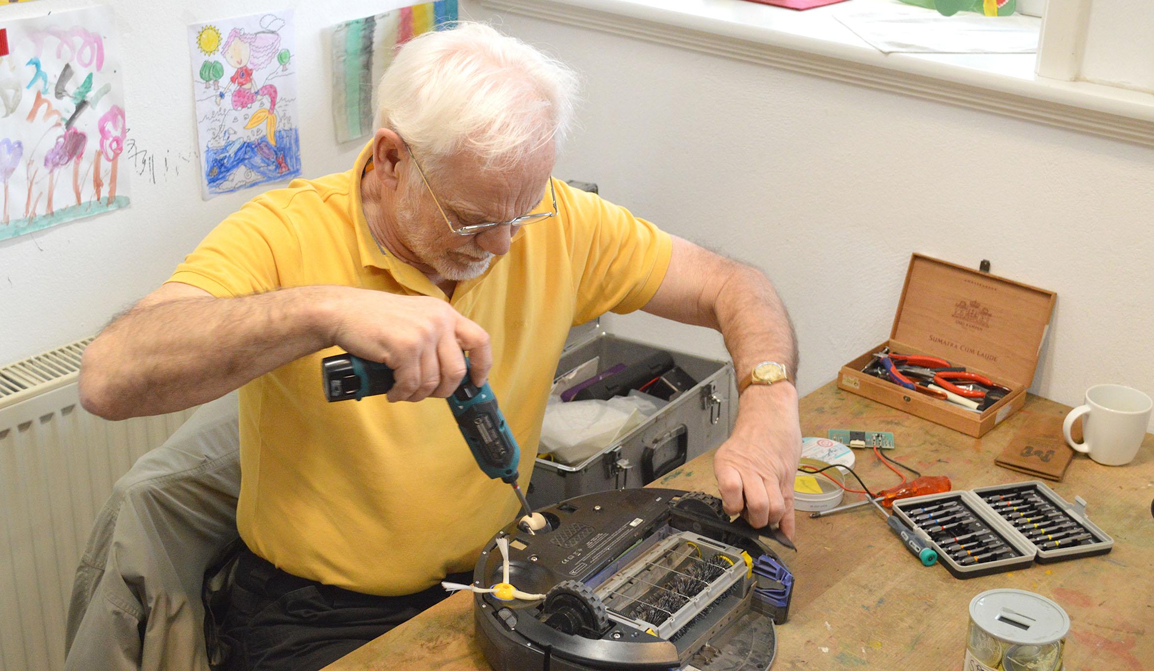 Das Bild zeigt einen Mann beim Reparieren.