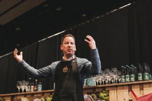 Sacha Mühlenbeck erklärt die Kultur des Gin und hält dabei die Arme hoch.