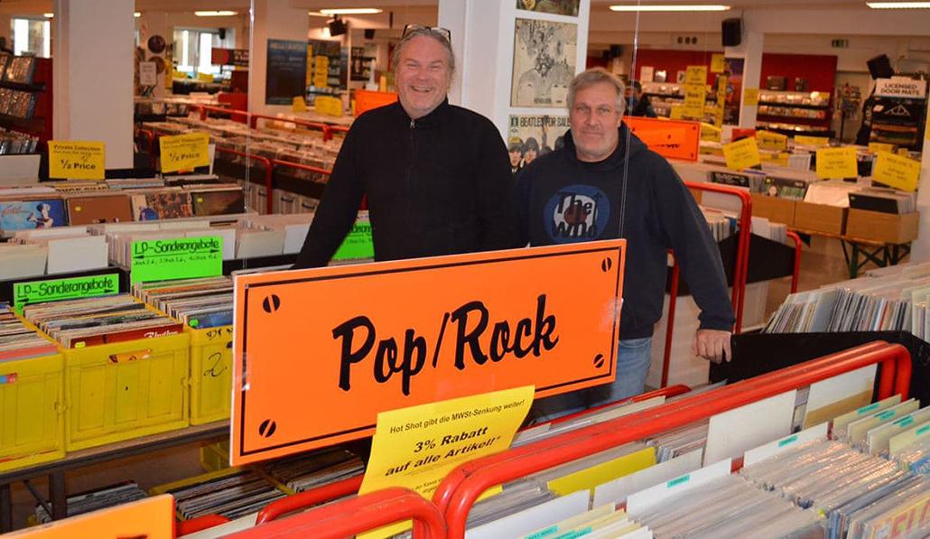 Norbert Fecker (links) und Volker Sieberg, Inhaber von Hotshot Records, stehen in ihrem Geschäft. Beide lachen.