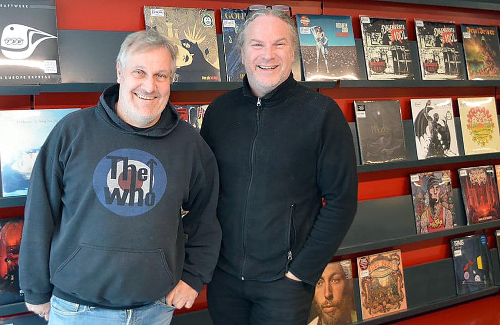 Volker Sieberg auf der linken Seite und Norbert Fecker stehen vor einer Wand mit LPs.