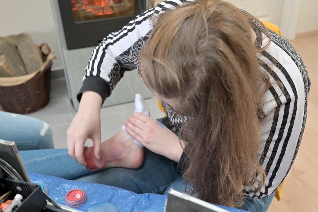 Lea Pünter schminkt eine Knöchel-Verstauchung.