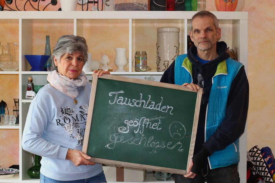 """Zwei Menschen halten ein Schild mit der Aufschrift """"Tauschladen geschlossen""""."""