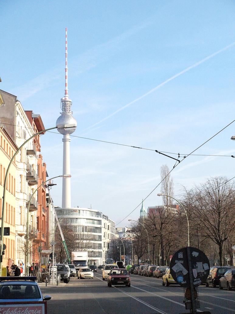 Eine Straßenszene mit dem Berliner Funkturm im Hintergrund.