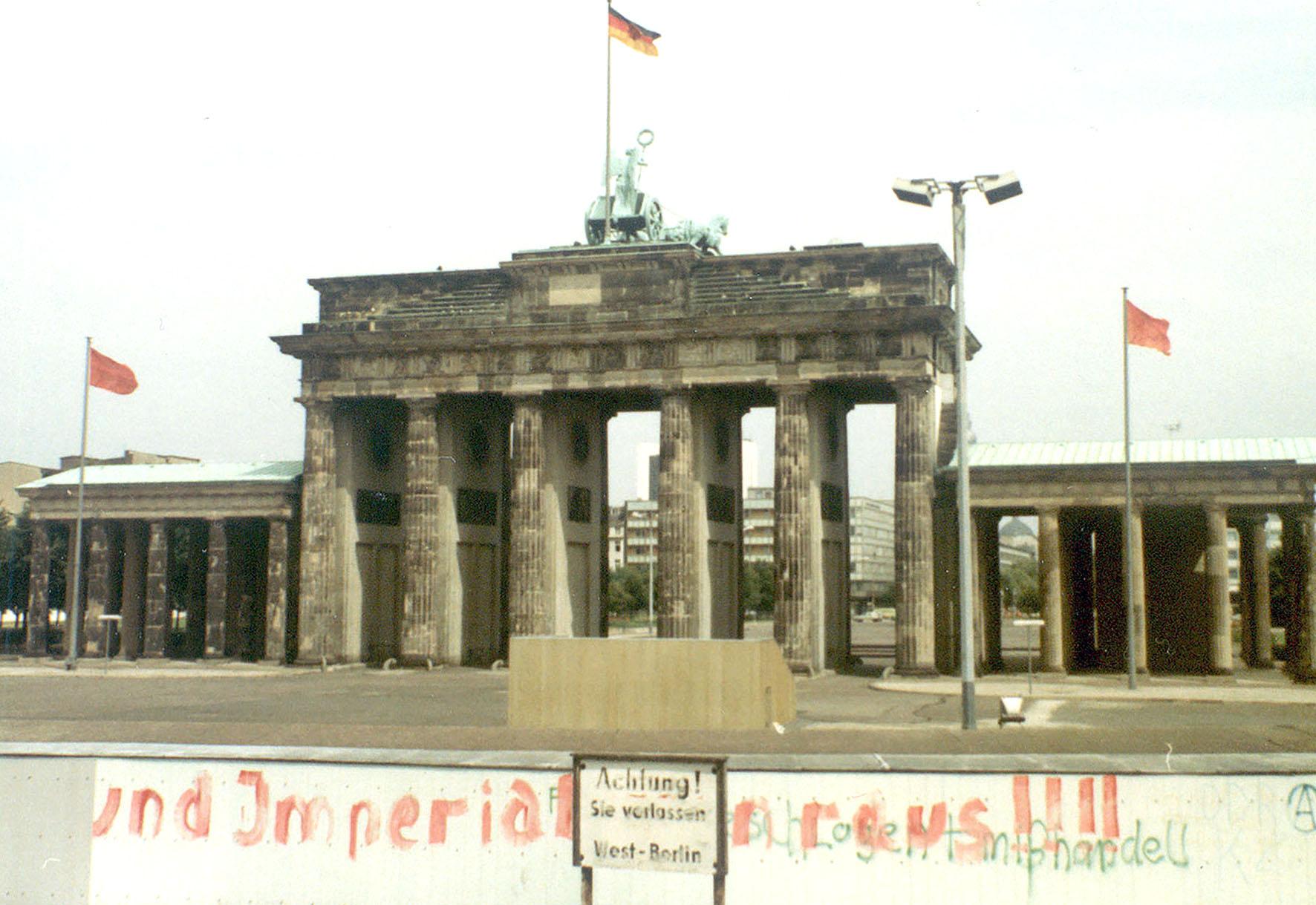 Das Brandenburger Tor mit einem Teil der Berliner Mauer im Vordergrund.