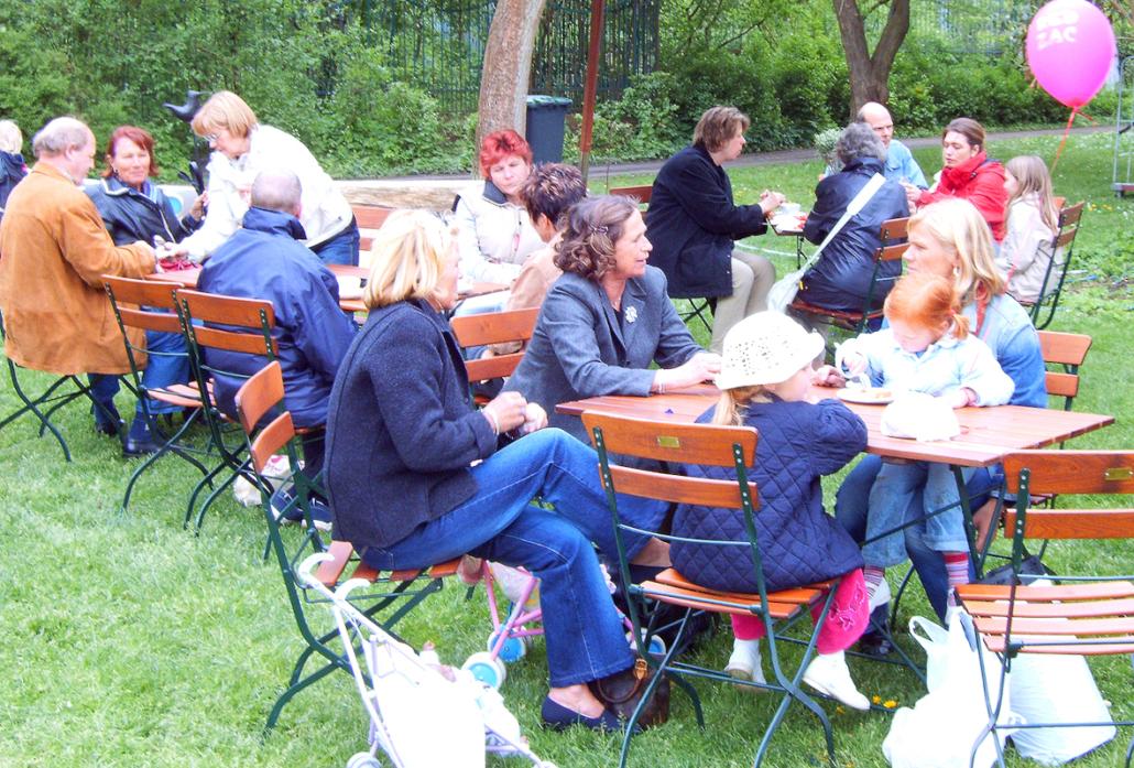 Menschen sitzen an Tischen und unterhalten sich.