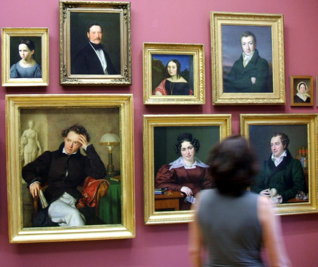 Eine Frau schaut sich Gemälde an.