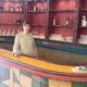 Eine Frau steht hinter einer Bar.
