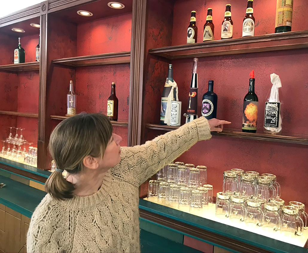Eine Frau zeigt auf Flaschen in einem Regal