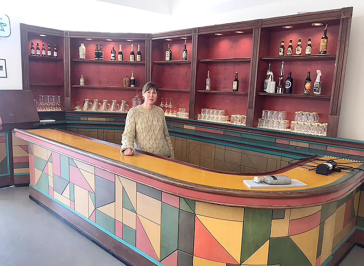 Eine Bar mit bunten Gestaltungselementen, dahinter steht eine Frau.