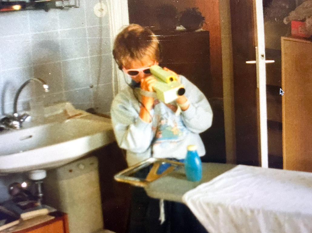 Ein Kind mit einer Kamera aus Pappkarton