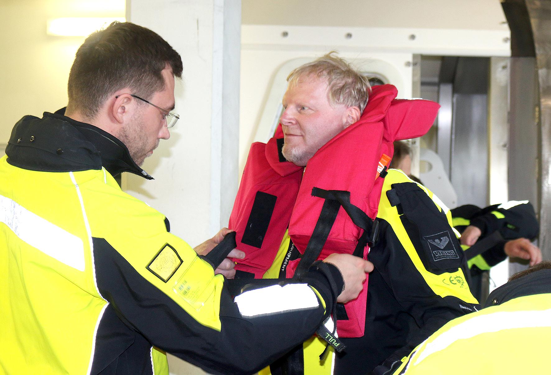 Ein Mann legt einem anderen eine Rettungsweste an.
