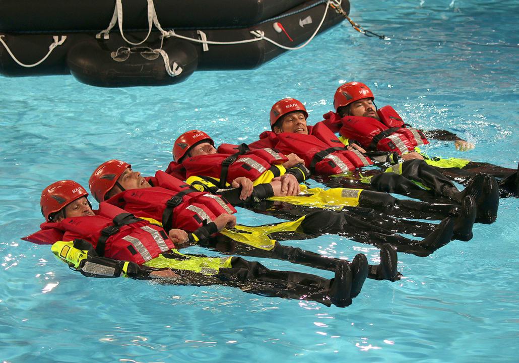 Männer in Überlebenanzügen mit Helmen auf dem Kopf treiben untergehakt im Wasser.