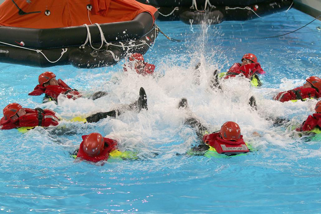 Männer treiben im Wasser plantschen. Sie tragen Überlebensanzüge und Helme.
