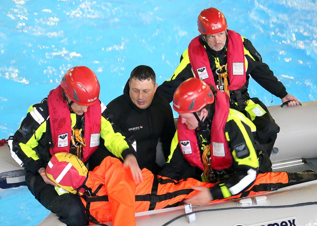 Männer in Überlebensanzügen sitzen in einem Boot und bergen eine Puppe.