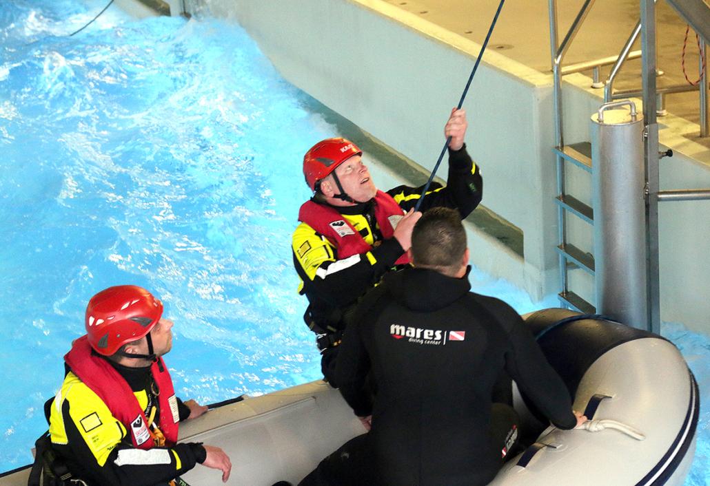 Ein Mann im Überlebensanzug greift nach einem Tau, um aus einem Boot auszusteigen.