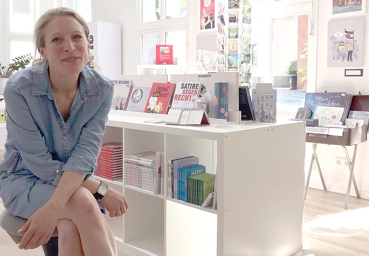 Dijana Nukic sitzt vor einen Büchertisch.