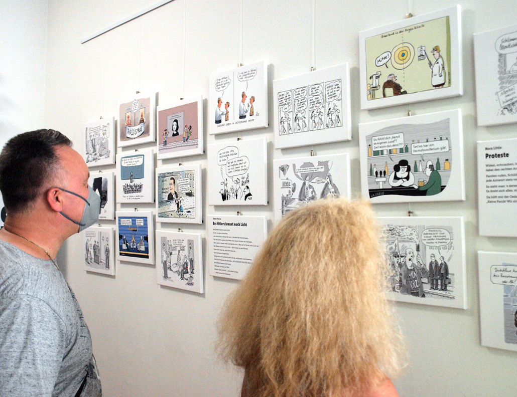 Eine Frau und ein Mann schauen sich Karikaturen an in einer Ausstellung an.