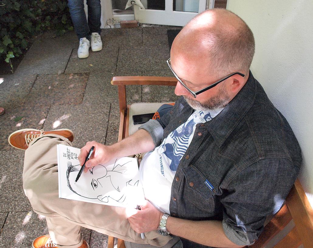 Ein Mann zeichnet in einem Buch.