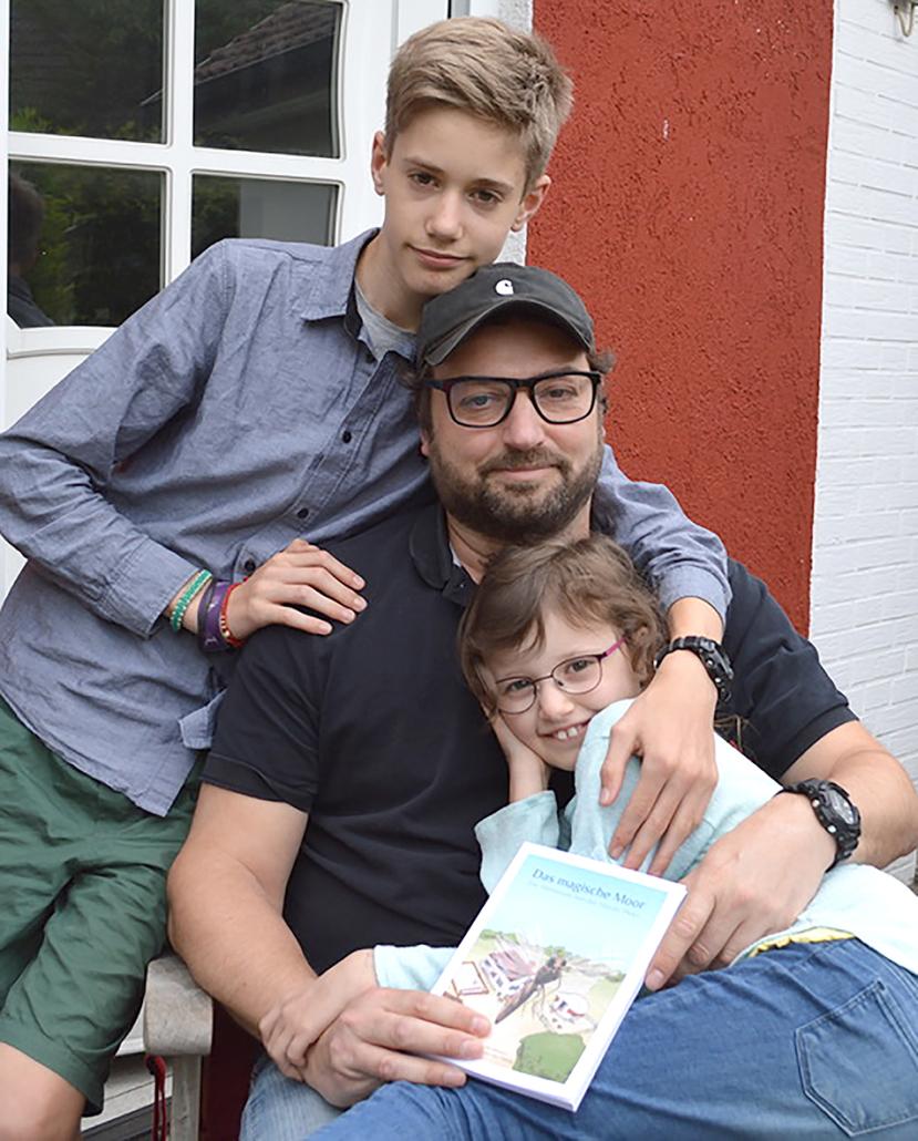 Zwei Kinder und ein Mann halten ein Buch.