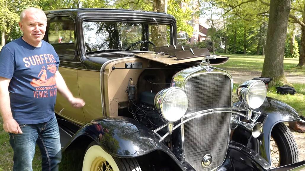 Ein Mann steht vor einem Oldtimer, einem Chevrolet, Baujahr 1932