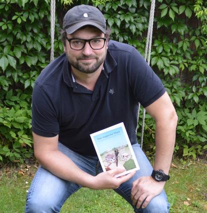 Ein Buchautor mit einem Buch.
