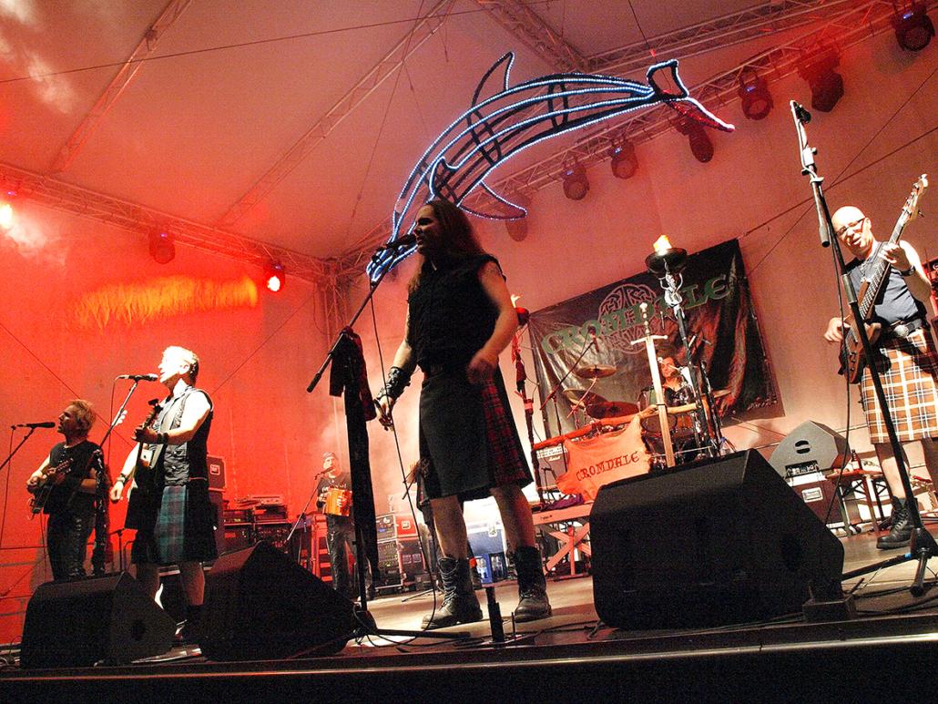 Eine Musikband steht auf einer Bühne.