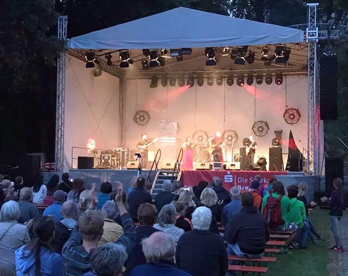 Eine Bühne mit Musikern und Zuschauern davor.