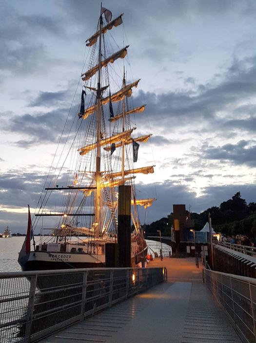 Ein Segelschiff liegt in der Abenddämmerung an einem Anleger..