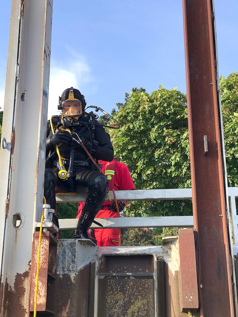 Ein Taucher sitzt auf einem Geländer