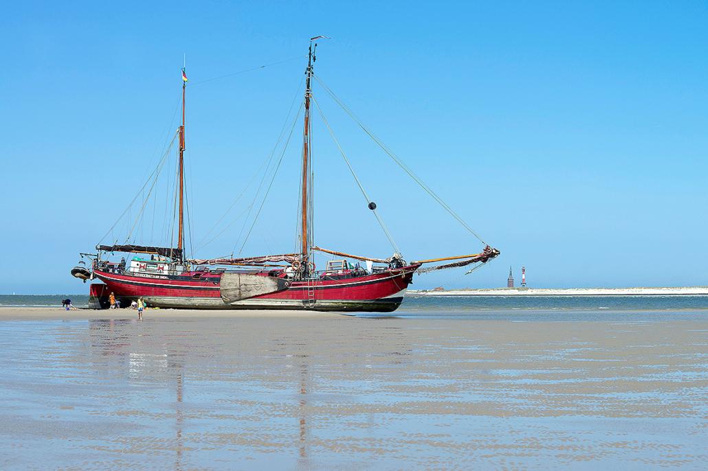 Ein Plattbodenschiff auf einer Sandbank.